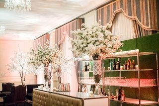 tufted-bar-with-glasses-and-bottles-on-shelf-in-front-of-hedge-wall-greenery-lace-around-glass-vases