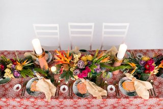 wedding-reception-orange-linen-palm-print-plates-tropical-centerpiece-pink-purple-yellow-flowers
