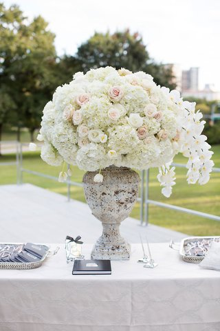 white-orchid-hydrangea-rose-flower-arrangement-in-urn-guest-book-and-programs-on-trays