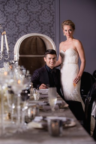 bride-in-a-strapless-inbal-dror-gown-groom-in-smoking-jacket-drinks-in-hand-at-reception-table