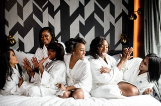 african-american-bride-with-bridesmaids-on-white-hotel-bed-with-robes-bridal-suite