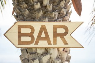 oceanfront-wedding-with-wood-arrow-sign-on-palm-tree-pointing-to-the-bar