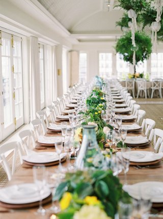 wedding-reception-wood-table-white-chairs-with-long-greenery-flower-runner-yellow-blooms-simple