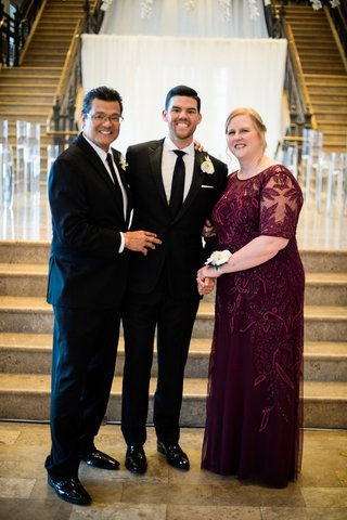 groom-with-father-and-mother-in-burgundy-dress-sheer-detail-beading-white-flower-corsage-on-wrist