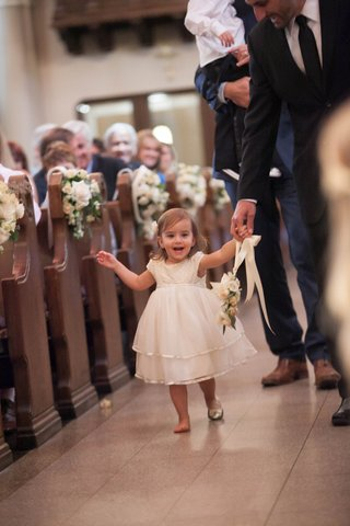 flower-girl-carrying-floral-wreath-down-catholic-church-aisle-with-one-shoe