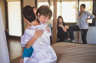 bride-with-high-bun-silk-bride-robe-hugs-mother-of-bride-before-the-wedding-ceremony