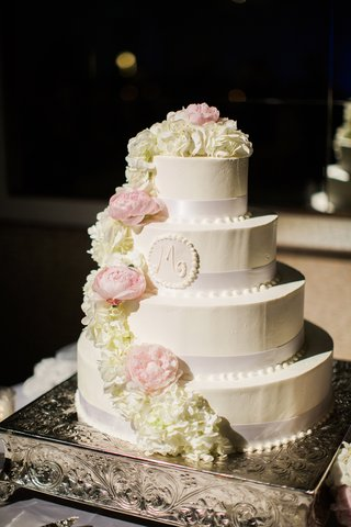 four-tiered-wedding-cake-with-ribbon-detailing-cream-roses-pink-peonies-initial-seal-with-frosting