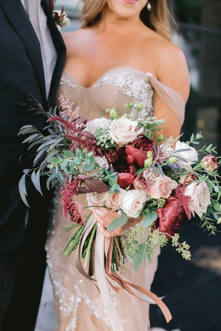 bride-in-blush-off-shoulder-inbal-dror-wedding-dress-foliage-fall-bouquet-burgundy-flowers