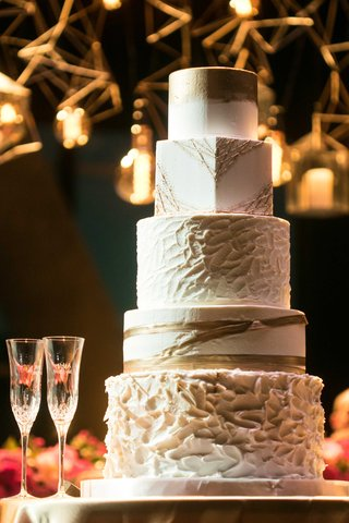 a-five-tier-white-and-gold-cake-each-tier-in-different-shapes-round-or-square-and-designs