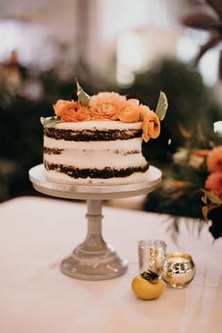 small-semi-naked-wedding-cake-with-fresh-orange-flowers-on-top-ranunculus-green-leaves-cake-stand