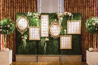 wedding-reception-escort-cards-in-gold-frames-gallery-wall-on-green-boxwood-hedge-wall