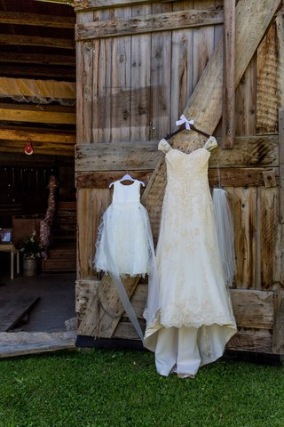 ivory-maggie-sottero-wedding-dress-hanging-on-barn-door-with-flower-girl-dress