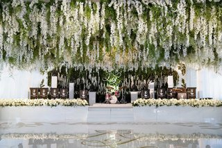 greenery-and-white-flower-installation-over-white-dance-floor-gold-monogram-live-band-stage-white