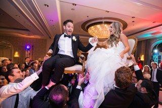 groom-in-lanvin-bride-in-reem-acra-during-the-horah-at-jewish-wedding