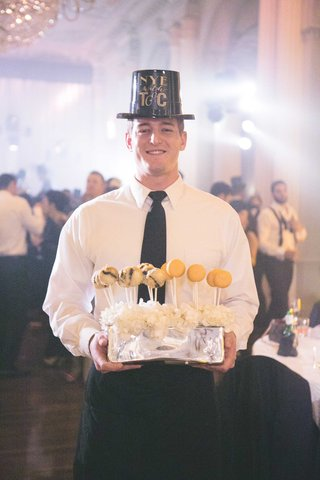 new-years-eve-wedding-waiter-with-black-new-years-eve-party-hat-holding-deep-fried-oreos-macarons