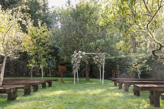 wedding-ceremony-wood-pews-benches-birch-branch-arch-with-greenery-pink-flowers