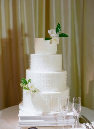 wedding-cake-four-layers-round-tier-with-fresh-flowers-on-top-and-bottom-layer-swiss-dot-ribbon