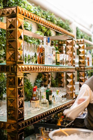 wedding-cocktail-hour-reception-bar-shelves-rose-gold-pyramid-studs-with-liquor-and-glassware