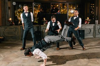 groom-and-groomsmen-in-tuxedos-do-a-choreographed-dance-at-reception-to-surprise-bride-with-worm