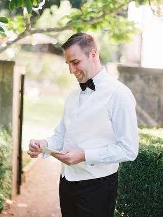 a-groom-in-tuxedo-with-black-bow-tie-smiling-while-he-reads-a-card-from-bride-outdoors