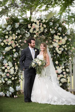 bride-in-lace-mermaid-gown-groom-in-charcoal-suit-at-floral-arch