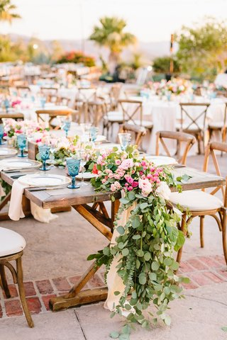 outdoor-wedding-reception-wood-table-wood-vineyard-chairs-blue-colored-goblet-greenery-pink-flowers