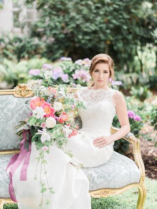 bohemian-inspired-bride-sits-on-vintage-blue-settee-jinza-couture-bridal-wedding-dress
