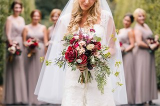 bride-displays-her-autumn-bouquet-featuring-wine-colored-florals-with-bridesmaids-in-background