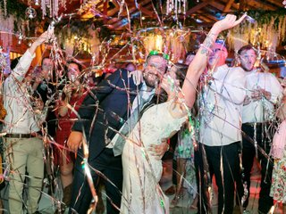 bride-and-groom-celebrating-with-guests-as-colorful-metallic-streamers-fall-down