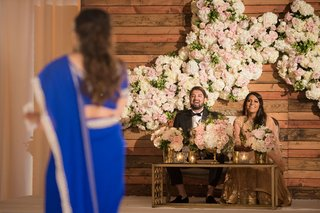 bride-and-groom-at-sweetheart-table-coffee-table-settee-wood-wall-pink-white-flowers