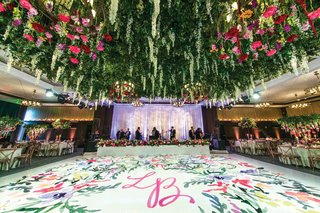 white-dance-floor-painted-with-floral-watercolor-and-pink-initials-lush-floral-ceiling-installation