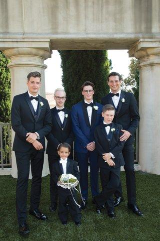 groom-in-navy-tuxedo-groomsmen-in-black-tuxedo-junior-groomsman-ring-bearer-with-white-tie