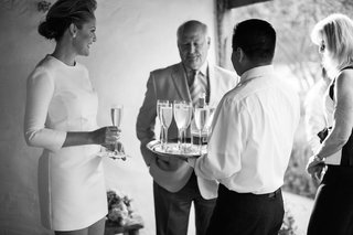 black-and-white-photo-of-bride-in-a-mini-mod-dress-with-3-4-sleeves-having-champagne-with-guests