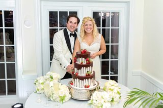 bride-and-groom-smile-with-grooms-cake-southern-white-cake-chocolate-ganache-dripping-down-berries