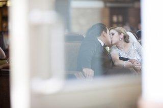 bride-in-beaded-jenny-packham-dress-kisses-groom-in-black-tuxedo