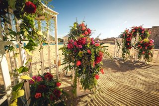 white-lanterns-with-cascading-floral-arrangements-of-red-and-orange-flowers-including-roses-on-beach