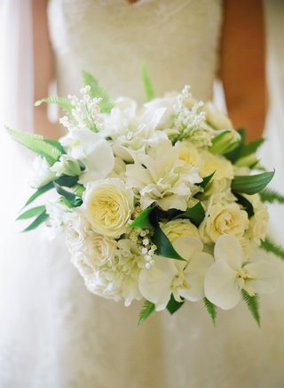 bride-holding-bouquet-of-white-garden-roses-orchids-lilies-lily-of-the-valley-and-greenery
