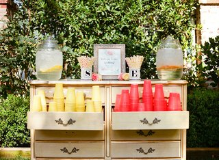 wedding-ceremony-outside-dresser-with-yellow-red-cups-fun-straws-peach-decor-water-dispenser