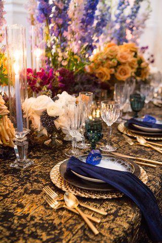 wedding-styled-shoot-periwinkle-tapered-candles-bright-flowers-teal-glassware-black-gold-linens