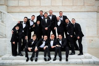 groom-and-groomsmen-ring-bearers-family-on-marble-steps-at-wedding-venue