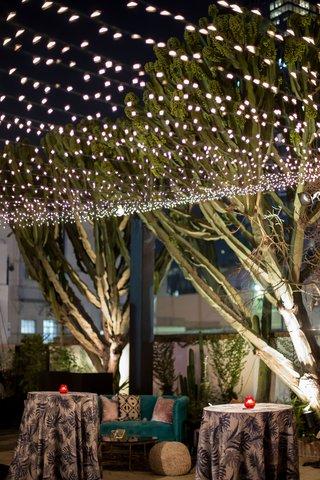 wedding-reception-lounge-area-tropical-blue-linen-with-teal-settee-velvet-pillows-poufs-string-light
