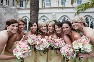 bridesmaids-in-yellow-dresses-holding-pink-bouquets