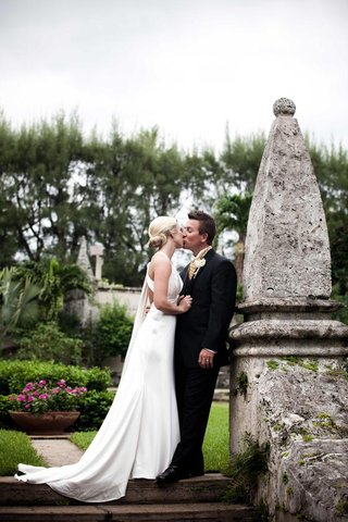 bride-and-groom-kiss-on-grounds-of-the-breakers