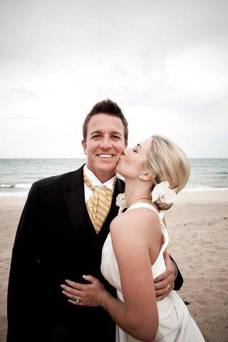 bride-kisses-grooms-cheek-on-beach-in-florida