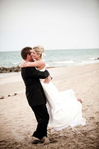 groom-lifts-and-spins-bride-on-beach
