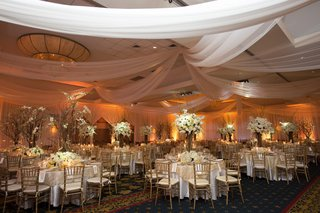 white-fabric-draped-from-ceiling-over-wedding-tables