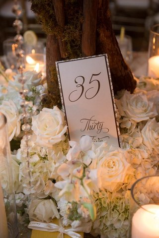 table-number-card-in-front-of-tree-trunk-with-brown-stationery