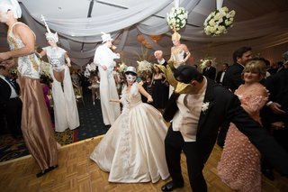 bride-and-groom-in-venice-style-masks-with-stilt-performers