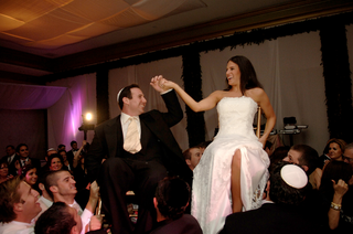 bride-and-groom-on-chairs-during-wedding-reception