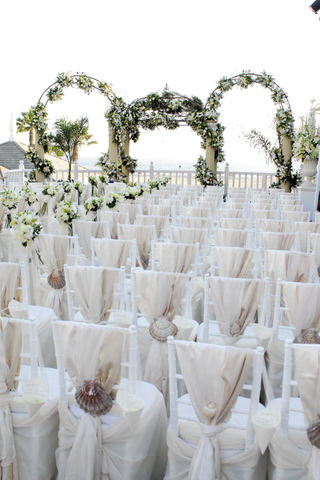 white-chairs-covered-in-fabric-and-large-seashells